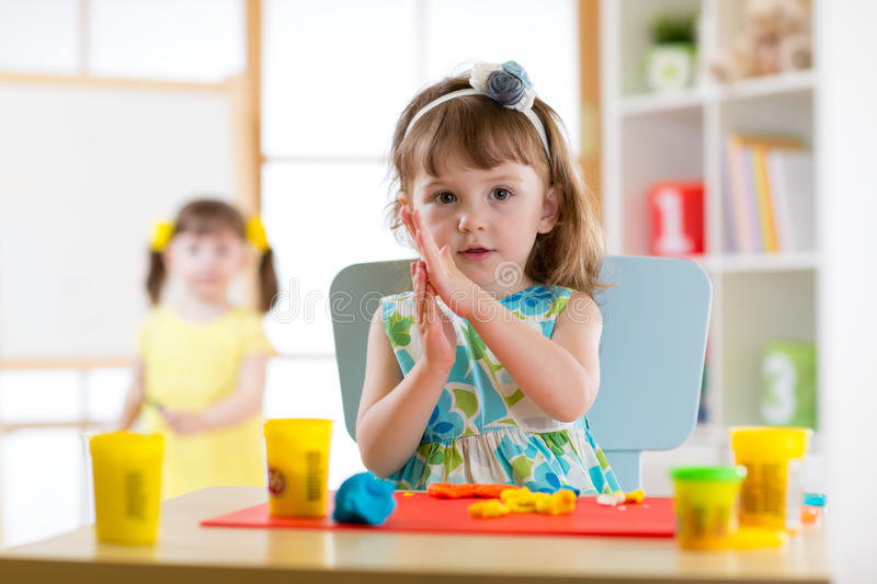 Preschooler girl having fun together with colorful modeling clay at a daycare. Creative kid molding at home. Children royalty free stock photography