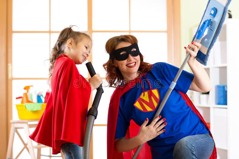 Preschooler girl and her mother dressed like superheroes. Middle-aged woman and kid playing while doing cleanup at home royalty free stock photography