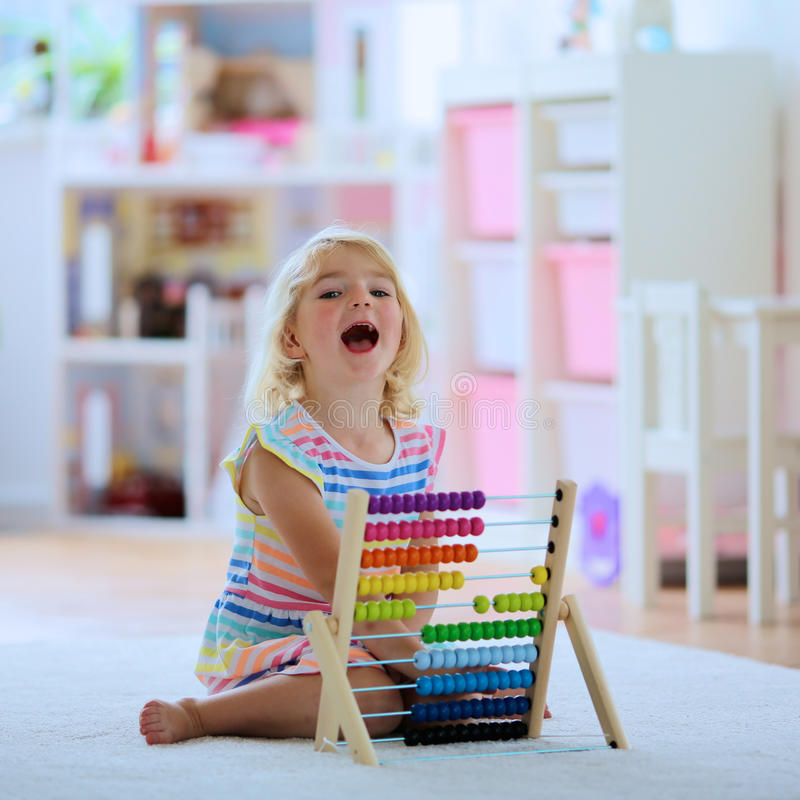Preschooler girl playing with abacus stock photos