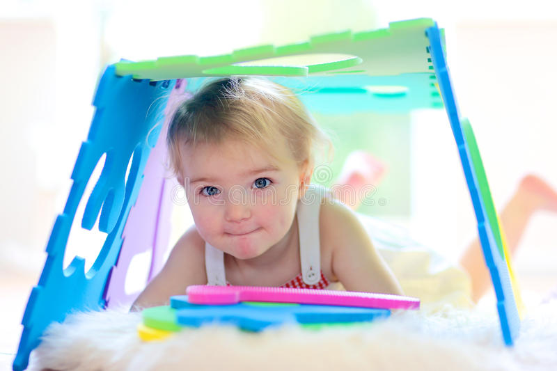 Preschooler girl playing at daycare. Adorable little child, happy blonde toddler girl playing hide and seek and learning numbers with colorful soft puzzles lying royalty free stock photo