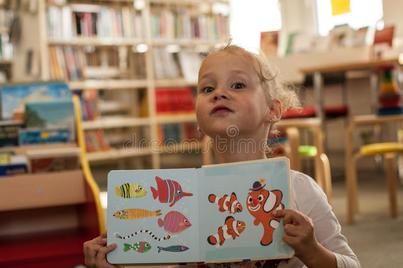 Preschooler little girl sitting and reading a book in library. Kid with books near a bookcase. Happy, cheerful and cute girl read stock photos