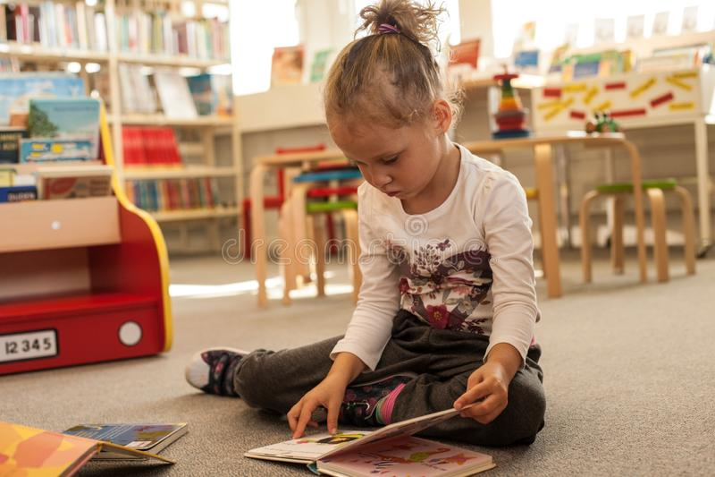 Preschooler little girl sitting and reading a book in library. Kid with books near a bookcase. Happy, cheerful and cute girl read stock images