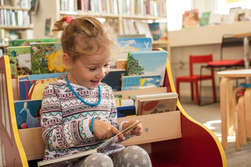 Preschooler little girl sitting and reading a book in library. Kid with books near a bookcase. Happy, cheerful and cute girl read stock photography