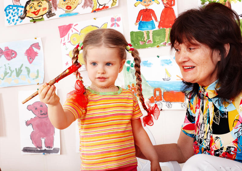 Preschooler and paintbrush with teacher draw. Preschooler girl and paintbrush with teacher draw paint in play room stock photo