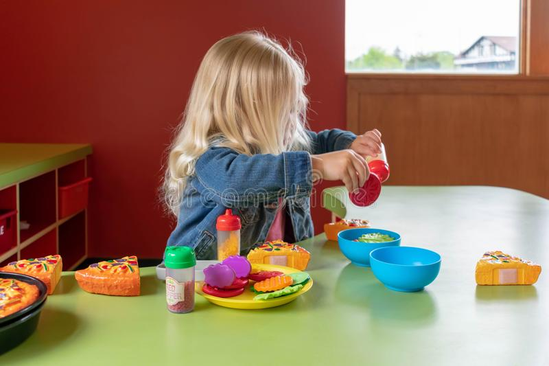 Preschooler playing with pretend food at learning center. Preschool age girl playing with pretend food at learning center stock images