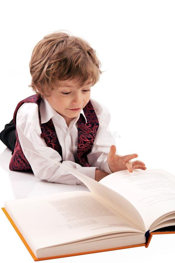 Preschooler que lê um livro ao encontrar-se no flo fotografia de stock