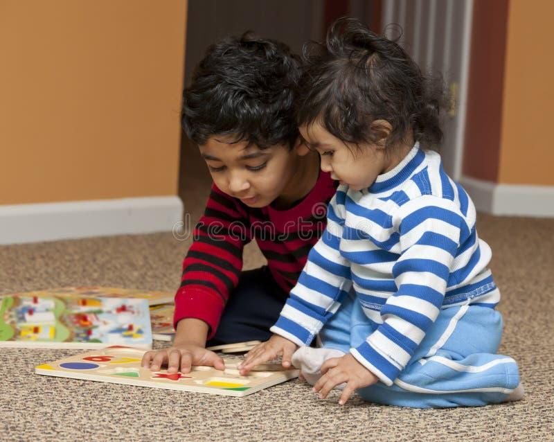 Preschooler que muestra rompecabezas de la hermana del bebé fotografía de archivo