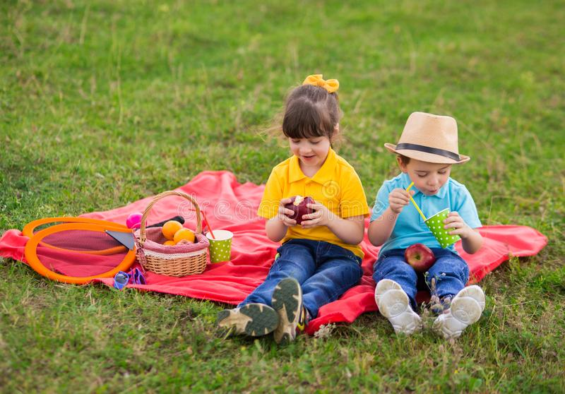 Preschoolers - a girl in a yellow polo with a bang and a boy in a blue T-shirt are sitting on a red plaid and eating apples and. Drinking juice. children`s stock photo