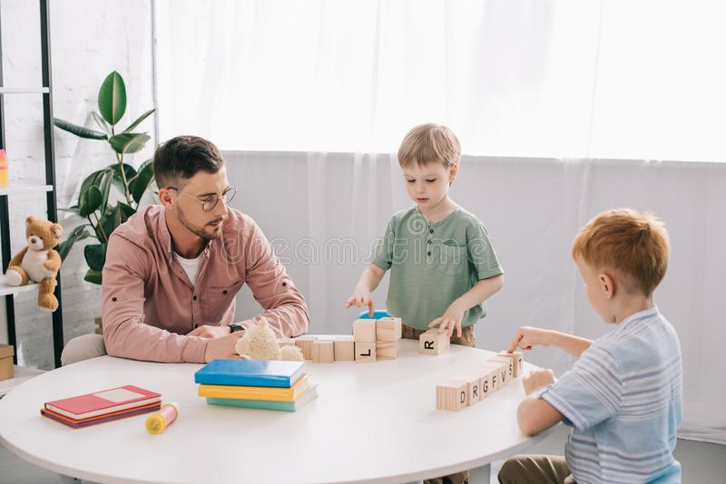 preschoolers playing wit h wooden block with teacher near by royalty free stock image