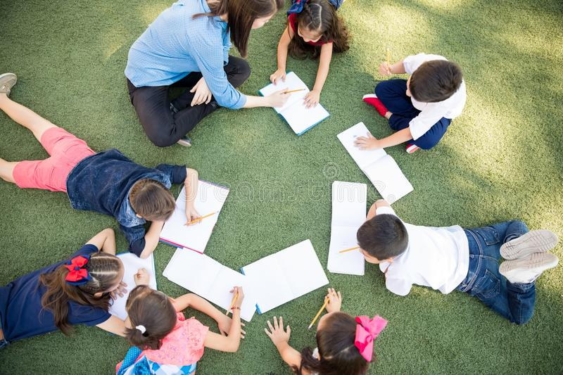 Preschoolers taking a class outdoors stock images
