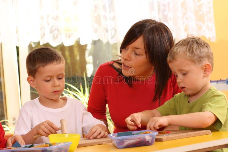 Preschoolers with wooden block stock photography