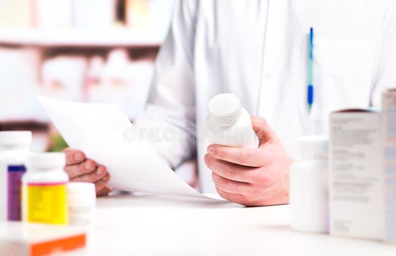 Prescrição da leitura do farmacêutico com a garrafa da medicina e de comprimido fotografia de stock royalty free
