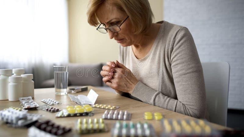 Prescrição da leitura da mulher, efeito secundário da medicamentação, apego da doença da idade avançada imagens de stock