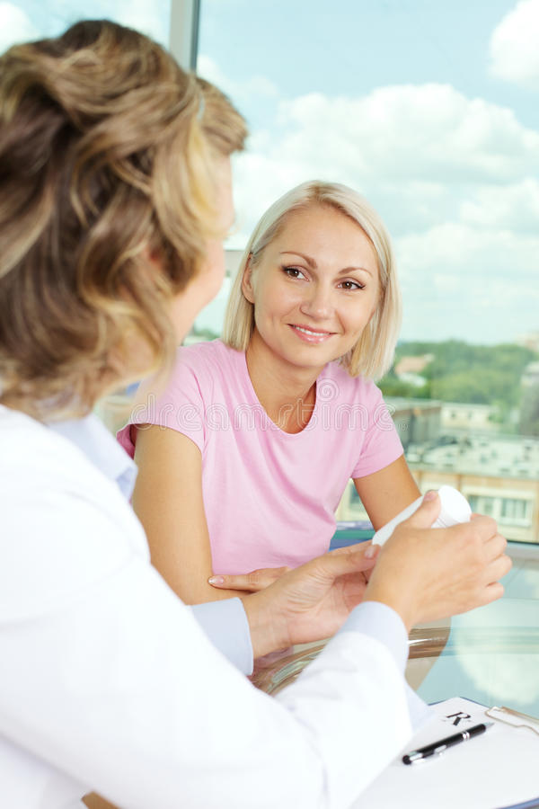Prescribing vitamins. Portrait of confident practitioner prescribing vitamins to patient in hospital royalty free stock images