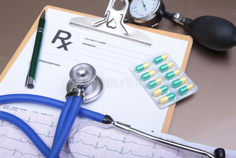 Prescripción de RX, corazón rojo, píldoras, metro de la presión arterial y un estetoscopio en la tabla imagenes de archivo