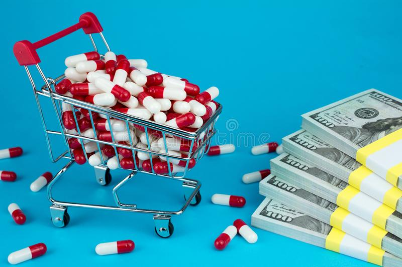 Prescription drug prices concept. shopping cart filled red medicinal capsules stock photography