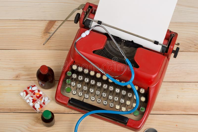 Prescription medicine or medical diagnosis - doctor workplace with stethoscope, pills, typewriter with blank paper on wooden table stock photo
