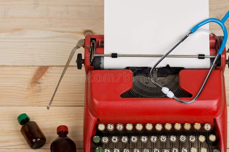 Prescription medicine or medical diagnosis - doctor workplace with stethoscope, pills, typewriter with blank paper on wooden table stock photography
