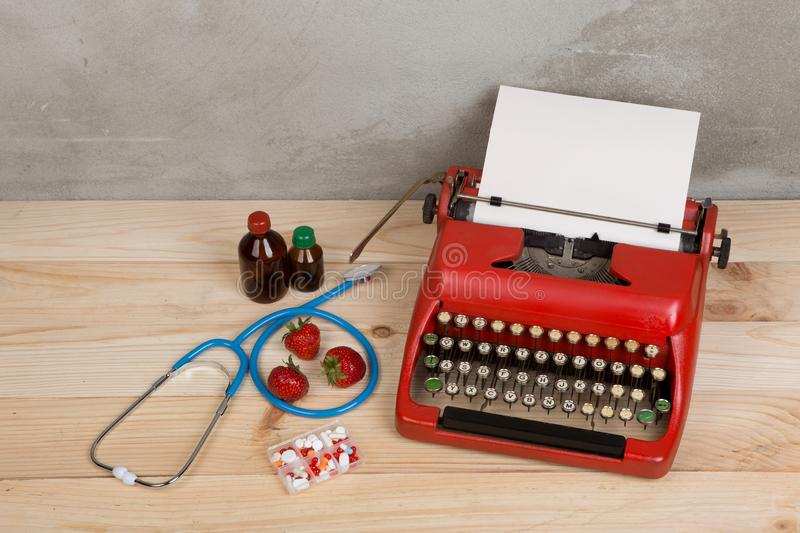 Prescription medicine or medical diagnosis - doctor workplace with blue stethoscope, pills, red typewriter, strawberries royalty free stock image