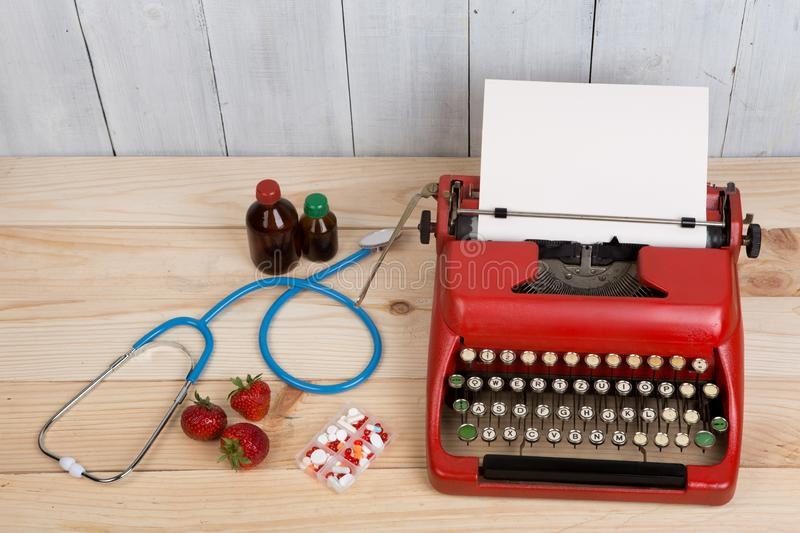 Prescription medicine or medical diagnosis - doctor workplace with blue stethoscope, pills, red typewriter, strawberries stock photography