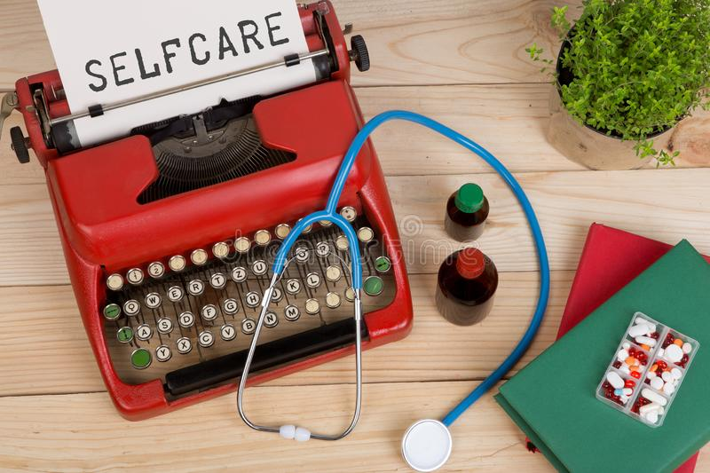 medical diagnosis - doctor workplace with blue stethoscope, pills, red typewriter with text Selfcare stock image