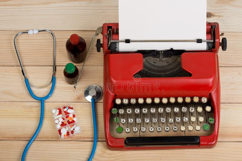 Prescription medicine or medical diagnosis - doctor workplace with stethoscope, pills, typewriter with blank paper on wooden table stock photos
