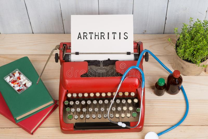 Prescription medicine or medical diagnosis - doctor workplace with stethoscope, pills, typewriter with text Arthritis royalty free stock image