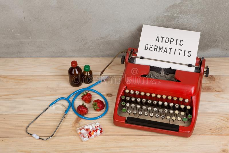 Prescription medicine or medical diagnosis - doctor workplace with stethoscope, pills, typewriter with text Atopic dermatitis, stock photo