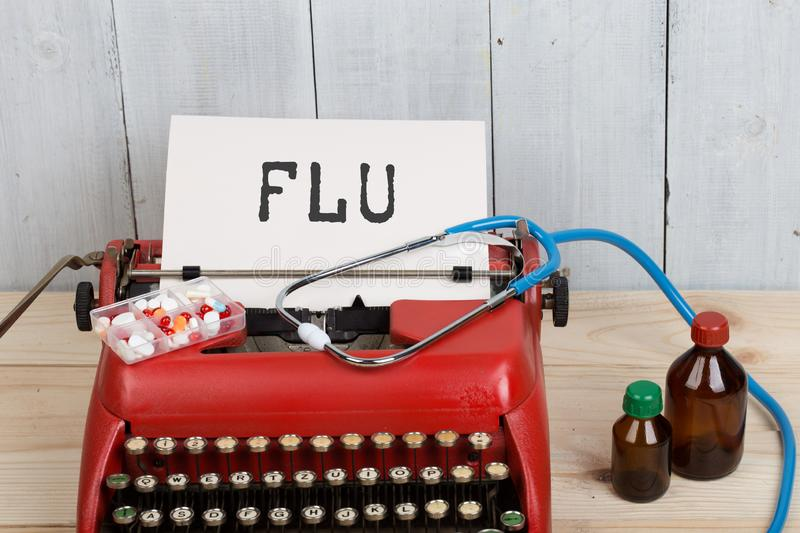 Prescription medicine or medical diagnosis - doctor workplace with stethoscope, pills, typewriter with text FLU. On wooden table, concept, health, bottle, care stock photography