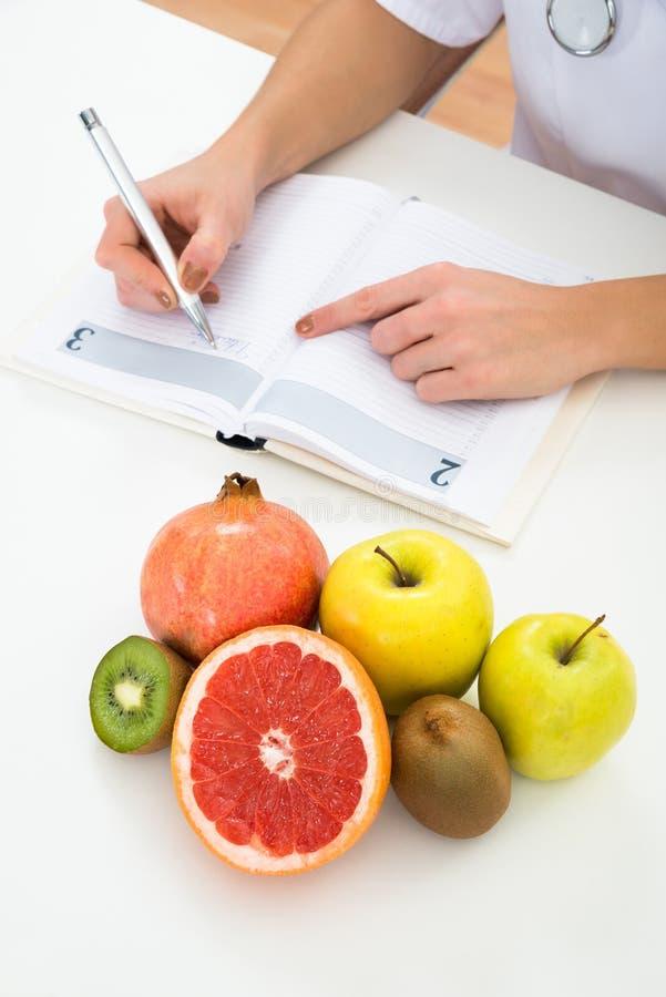 Download Prescrizione Di Scrittura Del Dietista Con I Frutti Sullo Scrittorio Immagine Stock - Immagine di femmina, fine: 55363343