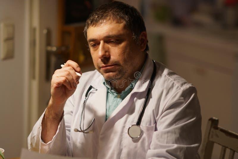 Prescrizione di scrittura di medico al suo scrittorio fotografia stock