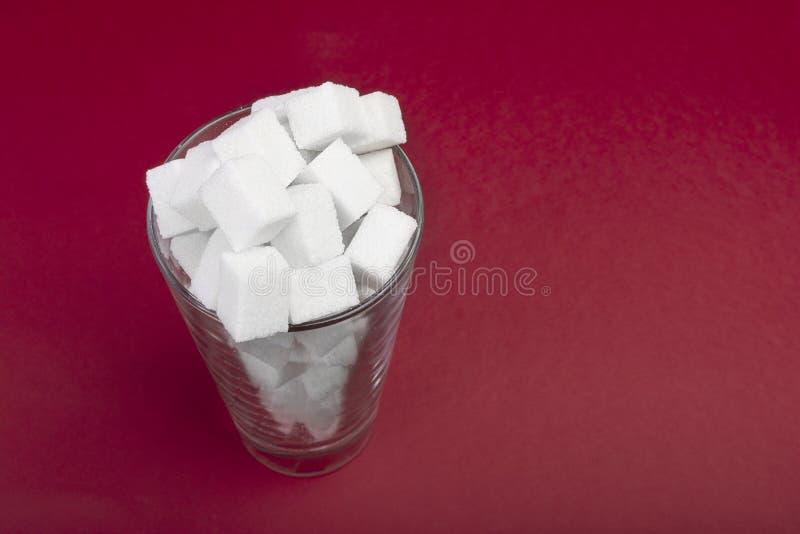 A presença de uma enorme quantidade do açúcar em um vidro da soda Vista superior Jn dos cubos do açúcar o vidro no fundo vermelho fotografia de stock