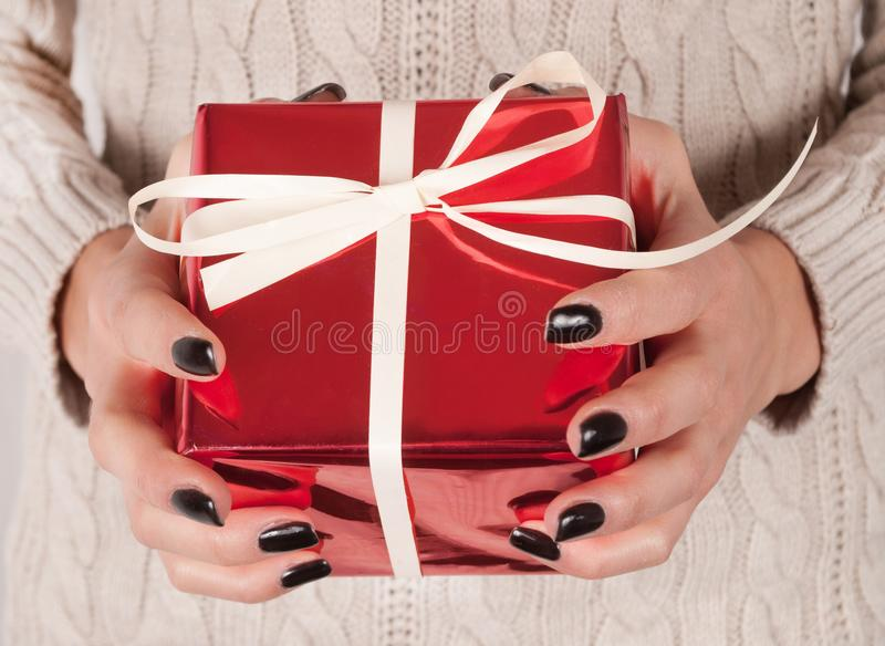 Present box with bow in young female hand with black nails and sweater clothing. Young Female holding red gift box with white tie bow in hands with black finger royalty free stock images