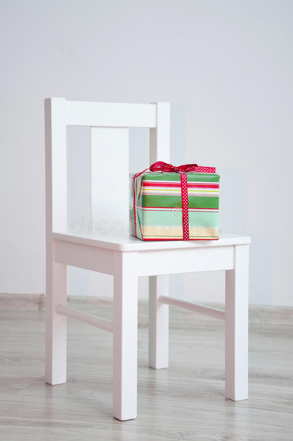 Present box on chair. Colorful red and green celebration present with dotted ribbon and bow lying on white geometric minimalistic style chair standing in an royalty free stock images