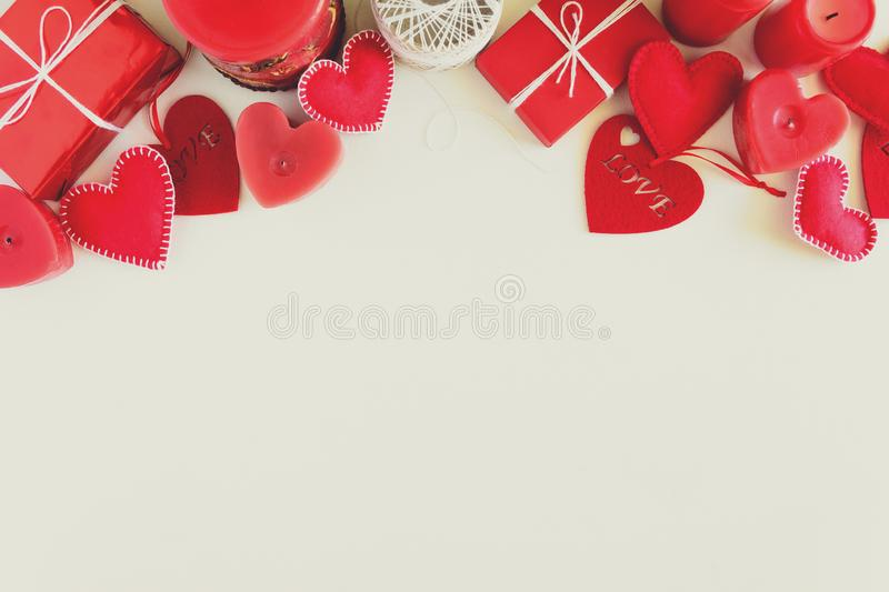 Present box with felt love hearts and candles on white wooden background. Valentine`s day celebration concept. Top view. Flat lay. Toned royalty free stock photo