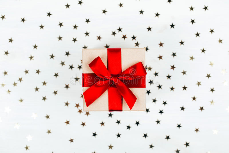 Present box with red bow. On white wooden rustic surface. Festive picture made in flat lay style with place for text stock images