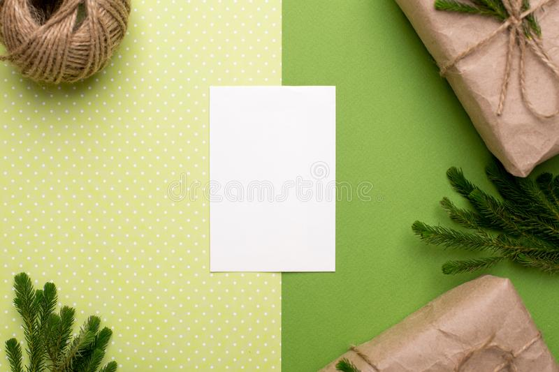 Present card and eco gifts with green plants in craft paper on a green background. Top view stock photo