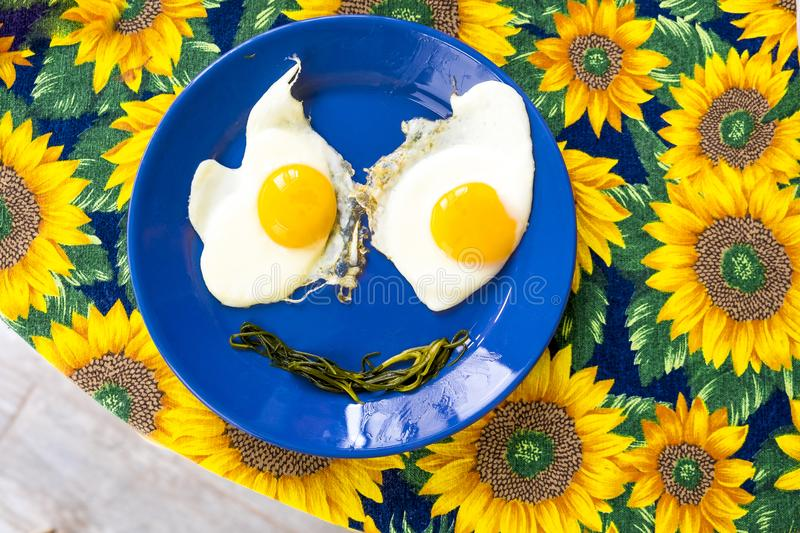 Present food plate - funny food faces smile fried eggs eyes vegetable mouth on blue dish yellow sunflowers cloth . stock photo