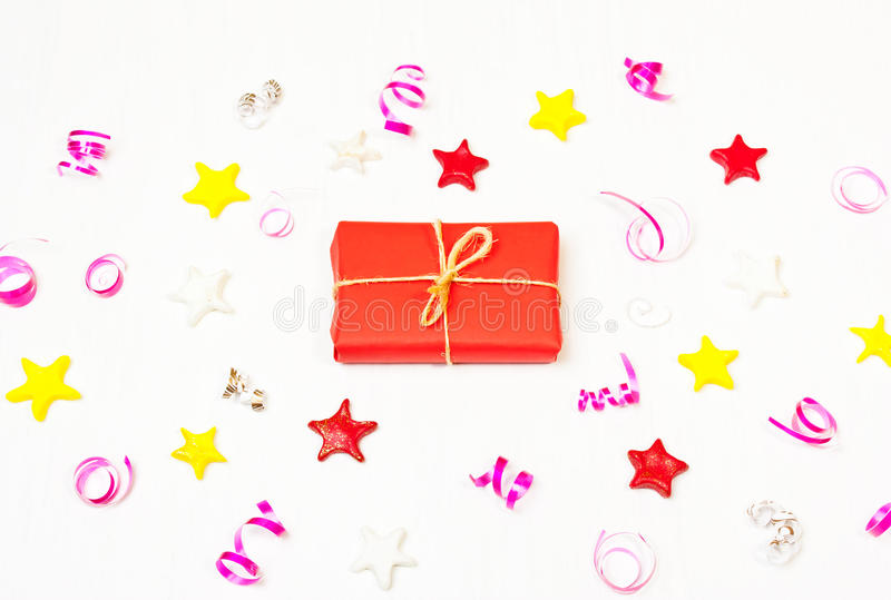 Present in the frame of stars, confetti on a white background. The composition of the present in red wrapping paper and stars, Christmas decorations. Christmas royalty free stock photography