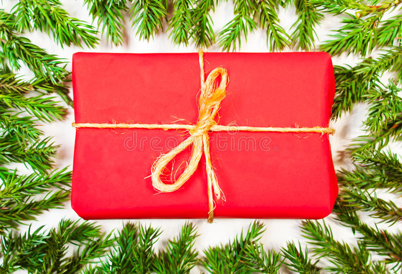 Present in the frame of tree branches. The composition of the Christmas tree and presents in red wrapping paper. Christmas, New Year`s background royalty free stock photos
