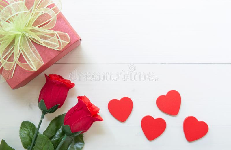 Present gift with red rose flower and gift box with bow ribbon and heart shape on wooden table, 14 February of love day stock photos