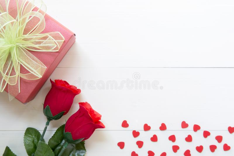 Present gift with red rose flower and gift box with bow ribbon and heart shape on wooden table, 14 February of love day royalty free stock image