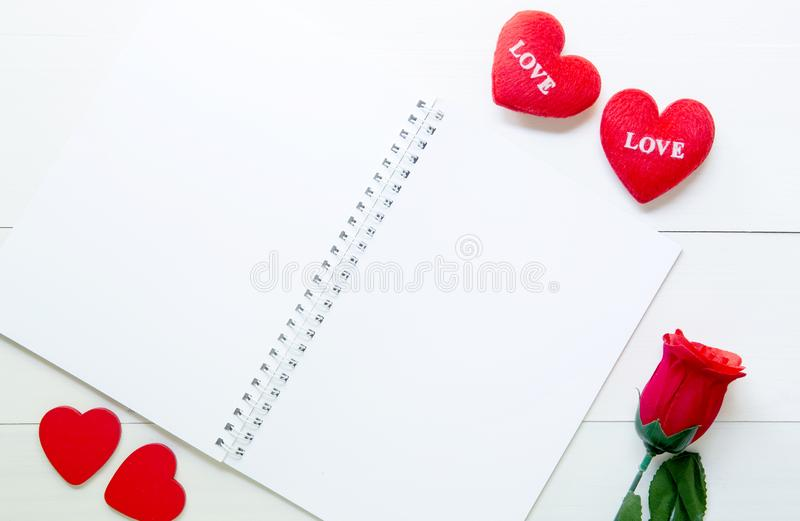 Present gift with red rose flower and heart shape and notebook on wooden table, 14 February of love day with romantic royalty free stock images