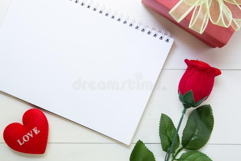Present gift with red rose flower and notebook and heart shape with copy space on wooden table stock photography