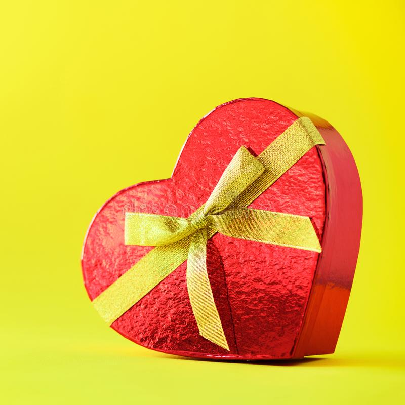 Present for her on yellow background. Valentines day. Red gift box in shape of heart. Copy space for text. Square crop. Romantic stock photography