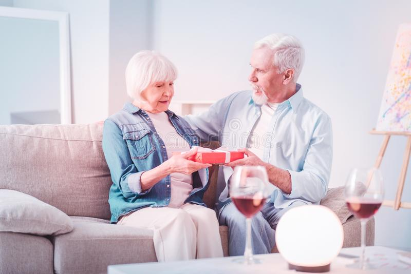 Retired woman feeling surprised receiving present from husband royalty free stock images