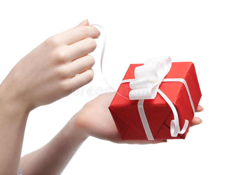 Present opening. Gift opening. Wrapped in red paper present with white bow, isolated on white stock images