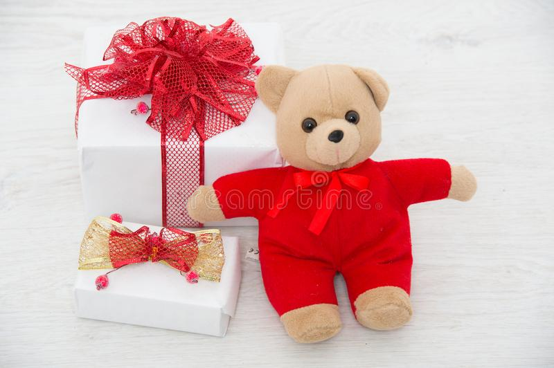 Present package on white background. Christmas box with red ribbon and valentines day bear. New year gift and toy. Xmas party celebration. Winter holiday and royalty free stock photo
