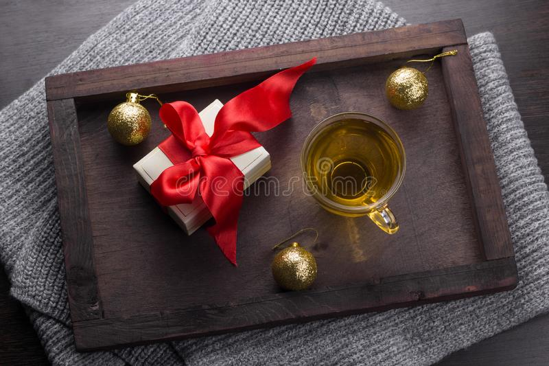 Present with red bow, tea cup and golden christmas balls. Top view present with red bow, tea cup and golden christmas balls stock images