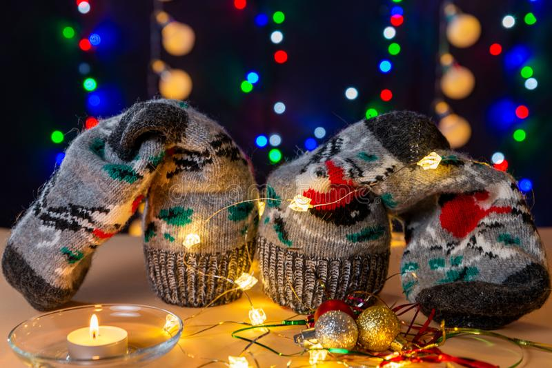 Present socks, lights, glowing candle and balss are on the light table/background. There are different colors lights. Present socks, lights, glowing candle and royalty free stock photos